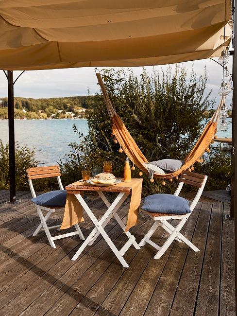 Moderne Terrasse Glamping Style Tisch Stuehle Haengematte