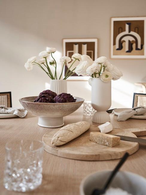 Dezentes Geschirr auf Holztisch und Vasen