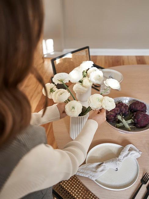 Frau arrangiert weiße Rosen in Vase