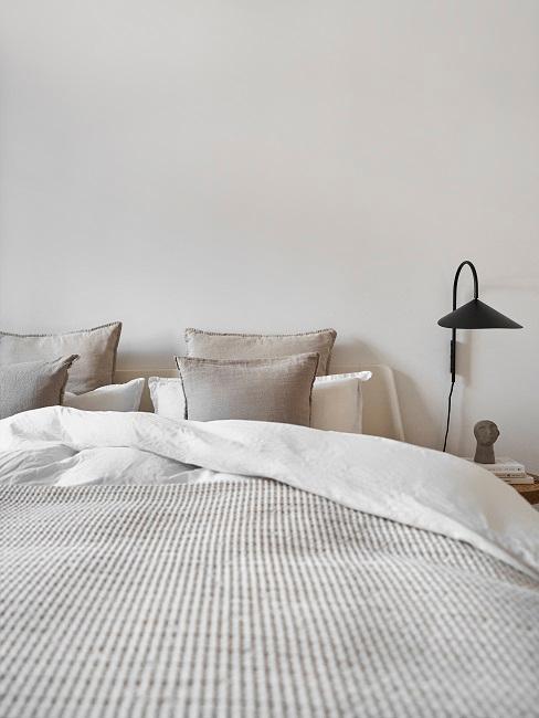 Bett mit ein paar Kissen und Nachttischlampe