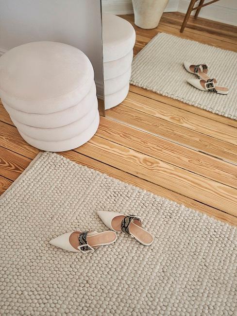 Beiger Teppich mit beigen Schuhen und Pouf