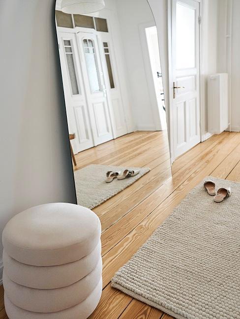 Flur minimalistisch eingerichtet mit Pouf und Spiegel