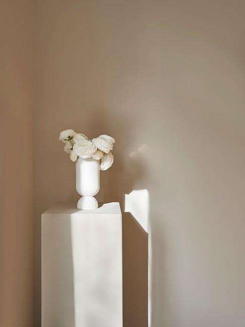 Weiße Vase mit weißen Rosen vor beiger Wand