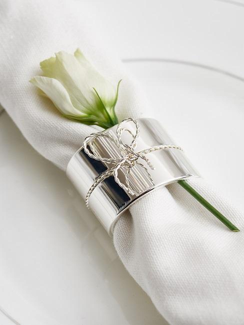 Weiße Serviette mit Serviettenring und weißer Rose
