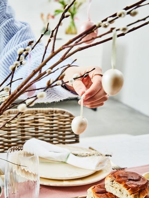 Frau hängt Ostereier auf