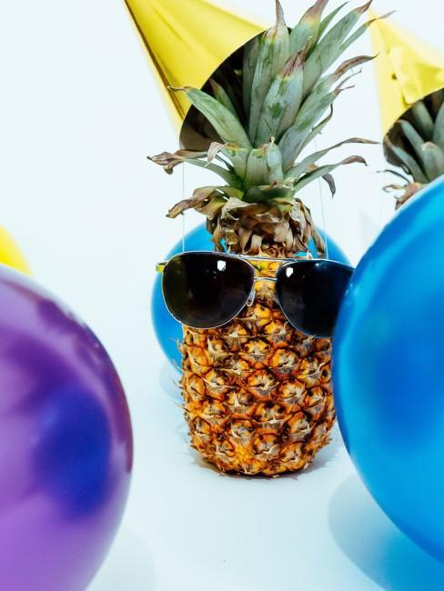Ananas mit Partyhut, Sonnenbrille und Luftballons