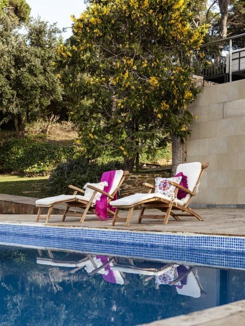 Liegestühle aus Holz am Pool