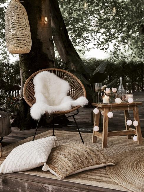 Auf einem Holzdeck stehen Gartenmöbel