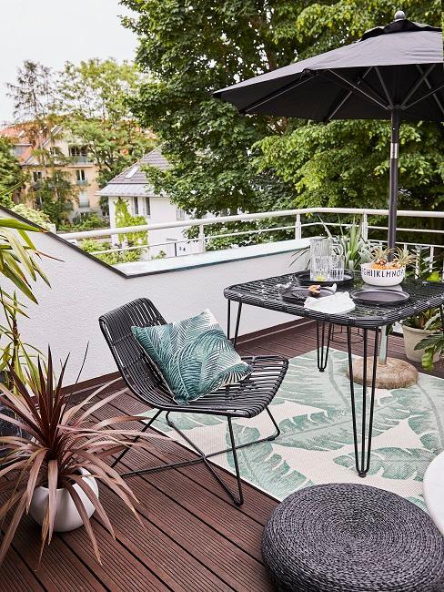 Balkon mit einem Schirm und einer Sitzgruppe