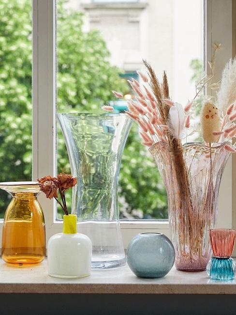 Alte bunte Vasen vor einem Fenster