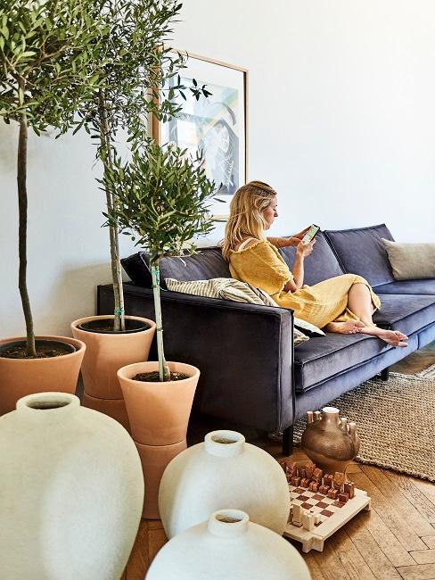 Große Terrakotta Töpfe mit Olivenbaum, dahinter eine Frau auf einem Sofa