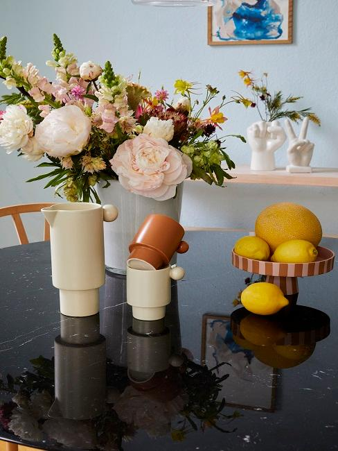 Drei Töpfe in Terrakotta stehen auf einem Tisch mit Blumen und Zitronen