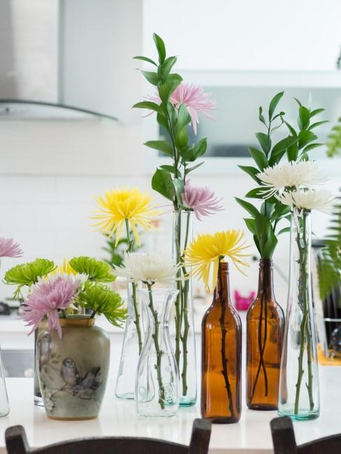 einzelne Blumen in Flaschen und Vasen dekoriert