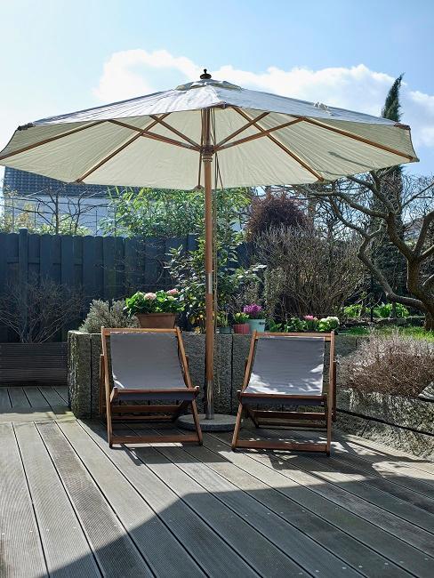 Zwei Klappstühle mit Sonnenschirm auf Terrasse