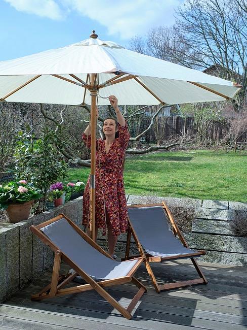 Frau steht zwischen klappbaren Sonnenstühlen und öffnet Sonnenschirm