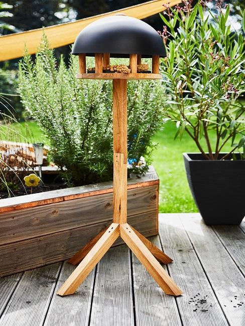 Vogelhaus aus Holz stehend auf Terrasse