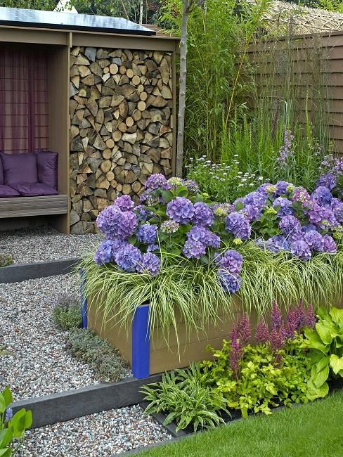 Hochbeet in Braun mit lila Blumen vor gestapeltem Holz