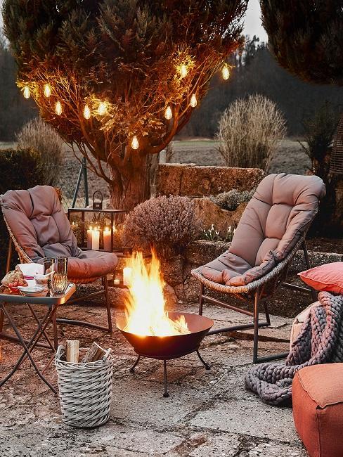 Feuerstelle mit Stühlen und Bodenkissen auf Terrasse