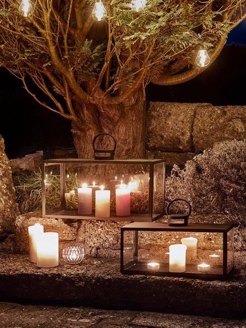 Viele Kerzen und Lichterkette auf Terrasse bei Nacht