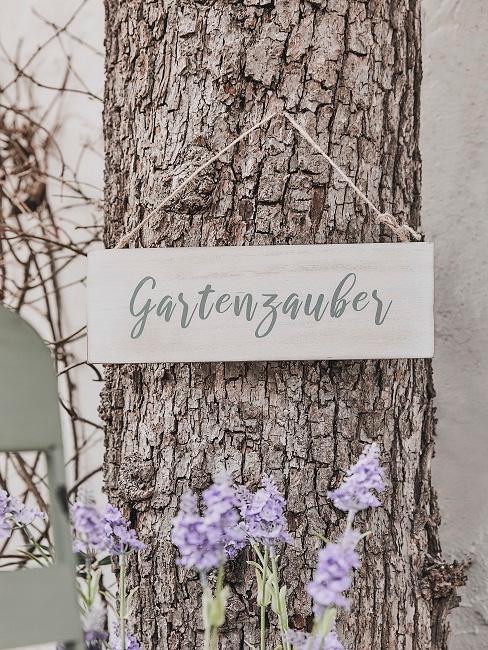 Holzschild an Baum mit Gartenzauber Aufschrift