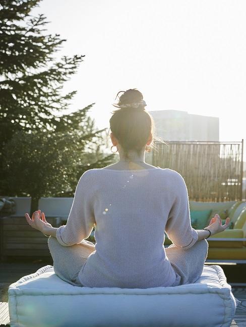 Frau auf Bodenkissen in Zen Pose