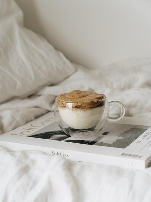 Schaumkaffee steht auf einer Zeitschrift in einer Glastasse