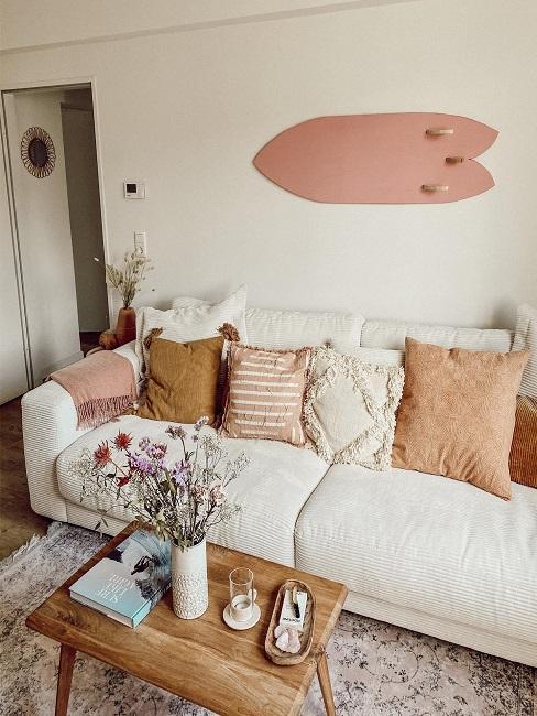 Helles Sofa mit bunten Kissen und Blumen