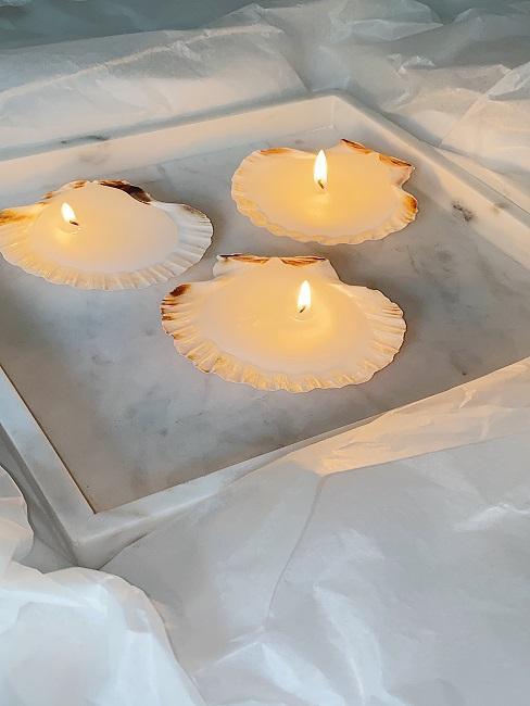 Kerzen in Muschelform auf Marmor Dekotablett