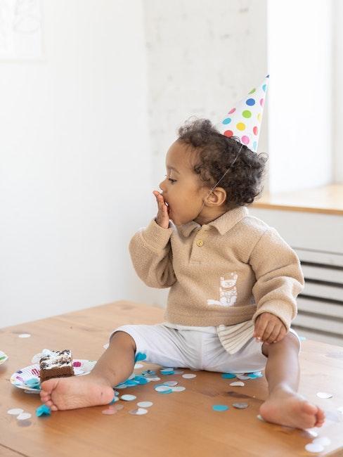 Kleines Kind mit Konfetti, Kuchen und Partyhut