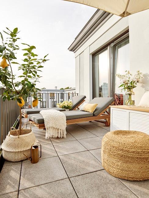 Balkon mit zwei Sonnenliegen und Pflanzen