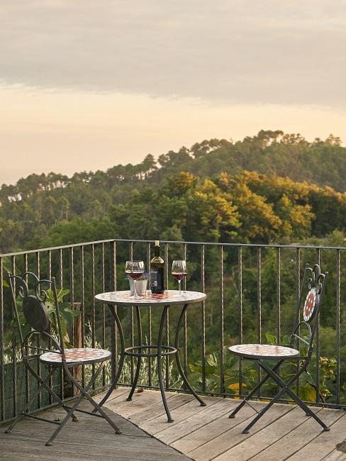 Balkon mit Tisch und zwei Stühlen und Blick auf einen Wald