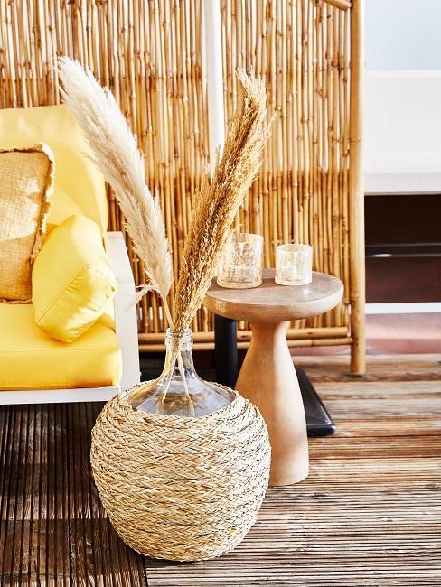 Vase mit Pampasgras vor einer Bambusmatte