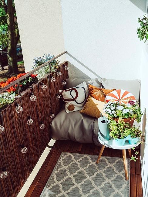 Balkon mit einer Bambusmatte und Sitzecke