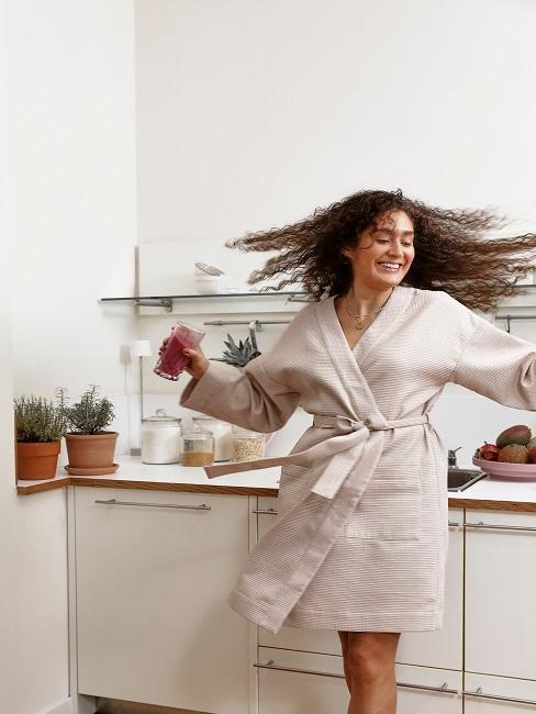Frau in Bademantel tanzt in Küche