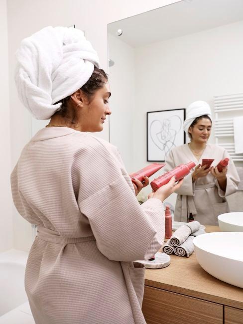 Frau in Badezimmer und Beauty Produkte in den Händen
