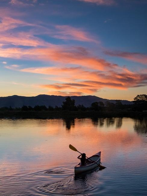 Mensch mit Kanu auf dem See in Abenddämmerung