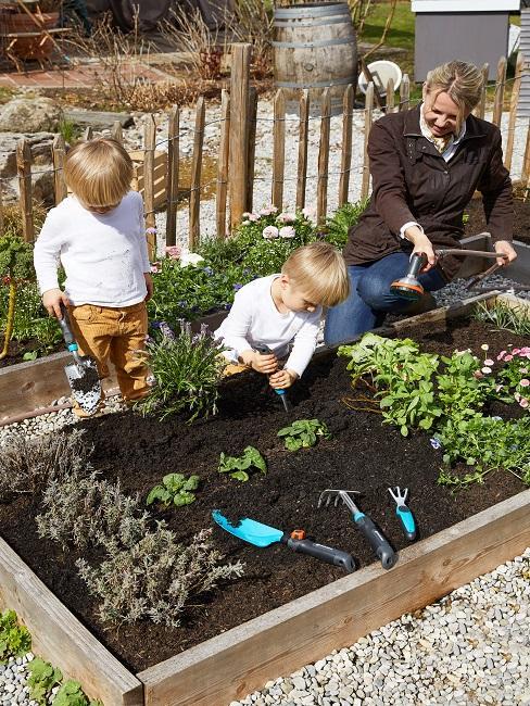 Frau und zwei Kinder pflanzen Blumen im Beet an