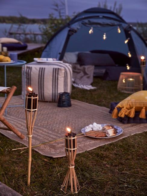 Blaues Zelt mit Sitzecke und Fakeln