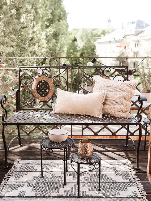 Bank mit Kissen und Outdoor Teppich auf einem Balkon