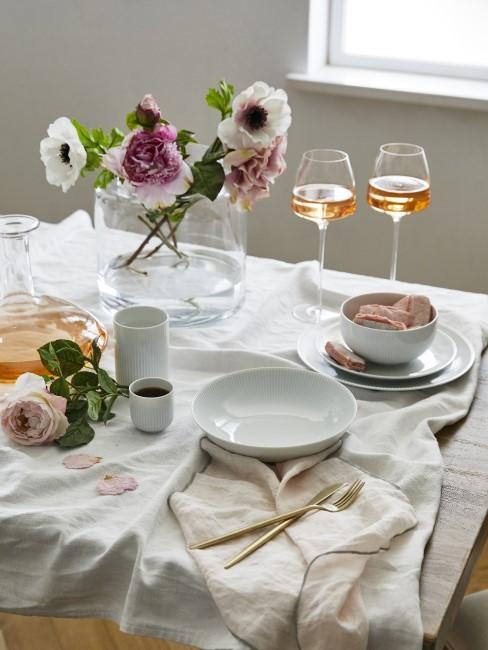 weiße Anemone und rosa Blume in Vase auf dem Esstisch