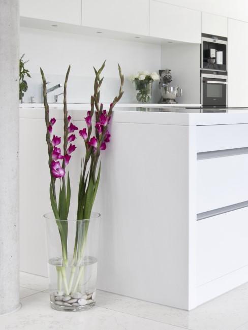 pinke Gladiolen in Bodenvase neben der Kücheninsel
