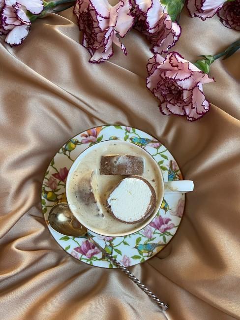 Rosa Nelke mit Kaffeetasse auf dem Bett
