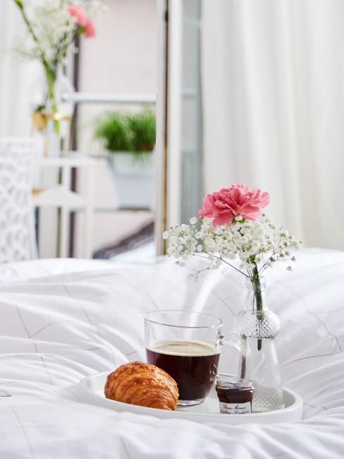 Rosa Nelke in Glasvase auf Tablett beim Frühstück im Bett