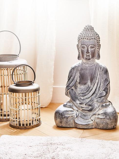 Buddha Figur neben Windlichtern