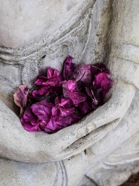 Hände eines Buddhas mit Blütenblätter