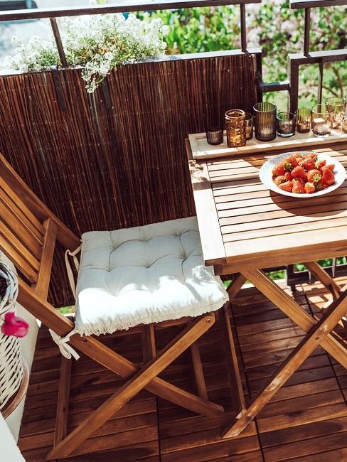 Kleiner Balkon mit einer Matte als Windschutz
