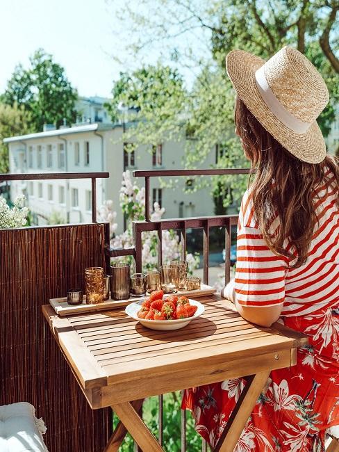 Frau die auf einem Balkon mit Windschutz sitzt
