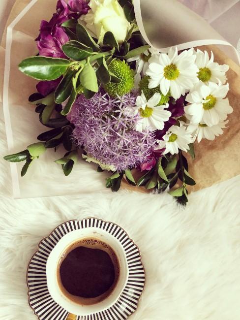 lila Blumenstrauß mit weißen und grünen Blumen plus Kaffeetasse