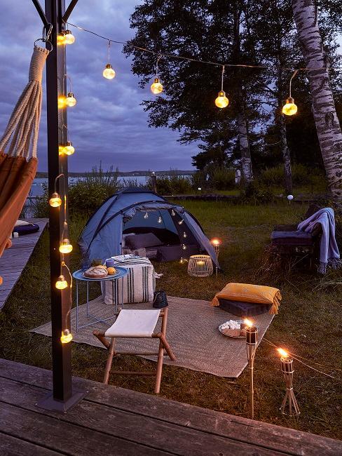 Zelt im Garten mit Lichterkette und Deko bei Nacht