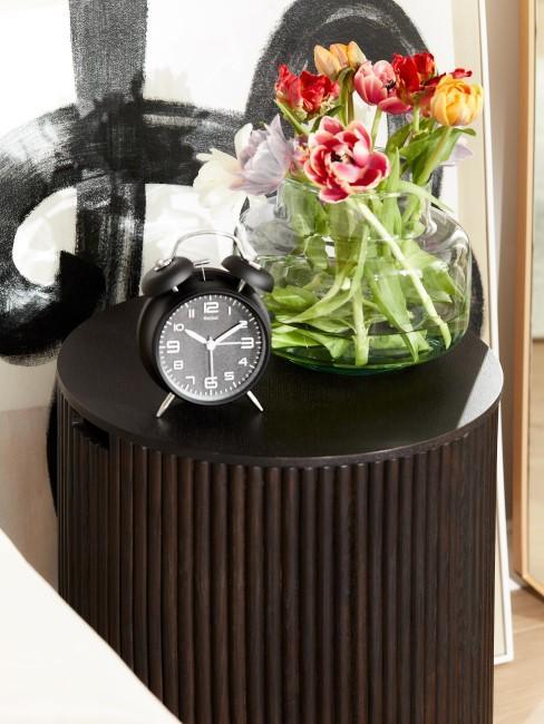 Nachttisch aus dunklem Holz mit Blumen